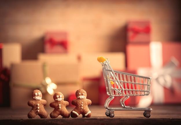 Пряничный человечек и тележка для покупок на столе с рождественскими подарками на фоне