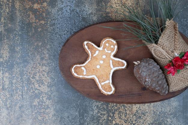 ジンジャーブレッドマンのクッキー、松ぼっくり、木の板に黄麻布の草。高品質の写真