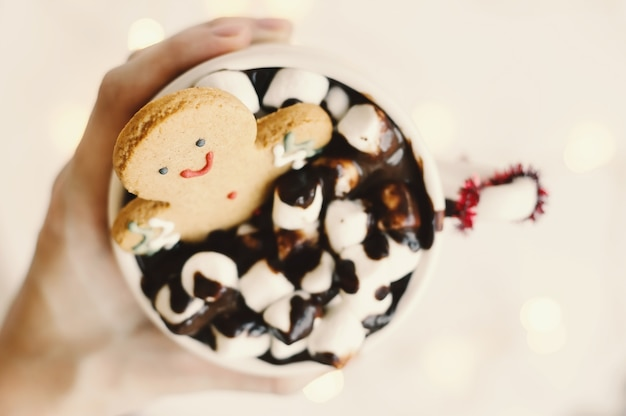 Gingerbread man in a cup with hot chocolate and white marshmallow
