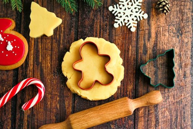 Пряничный человечек из имбирного пряника. украшение на деревянном фоне. приготовление рождественских пряников на темном фоне.
