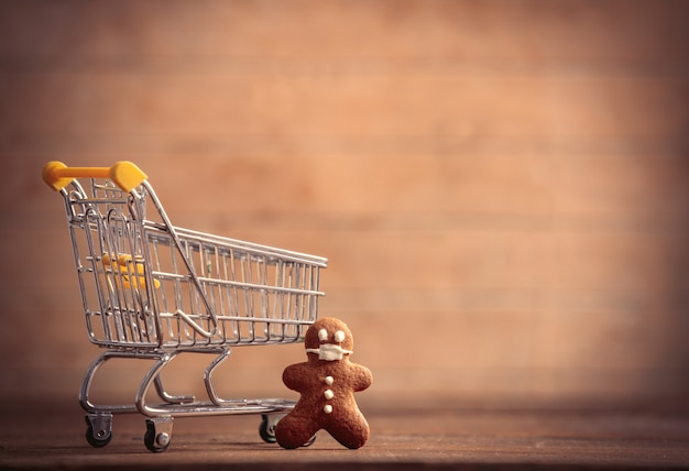 Gingerbread man in mask and cart on a wooden table