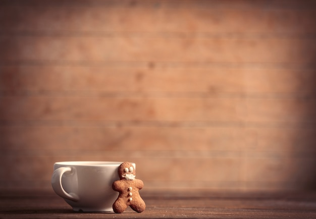 Gingerbread man in mask and cup on a wooden table