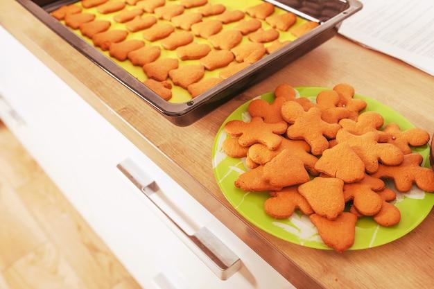 皿とベーキングパンにジンジャーブレッドマン。オーブンから出して。クリスマスのベーキング。休日、クリスマス、新年の準備。