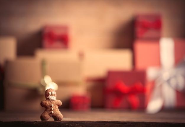 Пряничный человечек на столе с рождественскими подарками на фоне