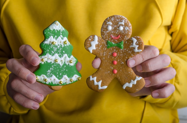 Gingerbread man in right hand and gingerbread tree in left hand