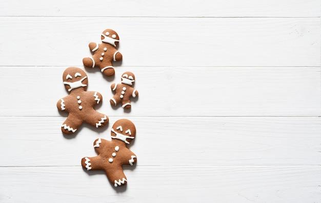 나무 배경에 얼굴 마스크와 진저 브레드 남자 쿠키. 전염병에 걸린 크리스마스