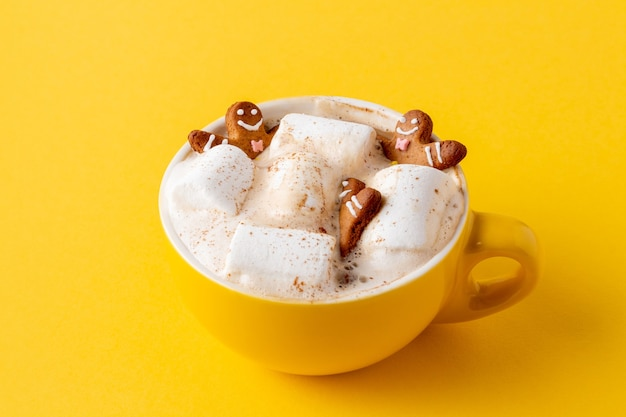 Gingerbread men in yellow cup of latte with marshmallow