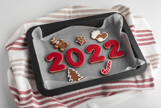 ジンジャーブレッド番号2022とベーキングシートに艶をかけられた砂糖のアイシングが付いているクリスマスクッキー。伝統的なベーキング。