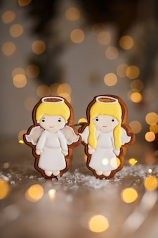 Gingerbread pair of little cute angels boy and girl in cozy warm decoration with garland lights