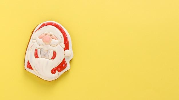 Пряник санта-клаус на праздничном желтом фоне, с новым годом, горизонтальная ориентация, копией пространства