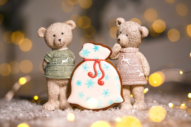 Gingerbread santa's bag of gifts and two decorative bears in cozy warm decoration with garland lights