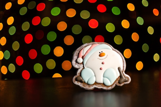 Gingerbread snowman over defocused colored lights of garland.