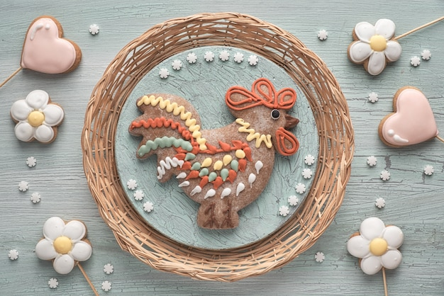 Gingerbreads shaped as a rooster bird, flowers and hearts on textured wood.
