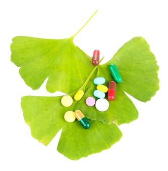 Листья гинкго билоба и таблетки на белом
