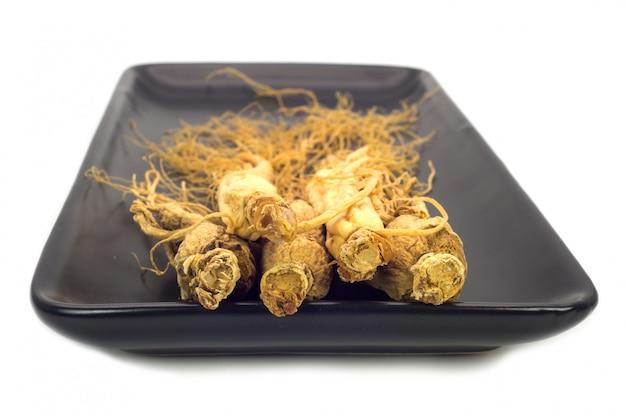 화이트 절연 검은 접시에 인삼 뿌리.