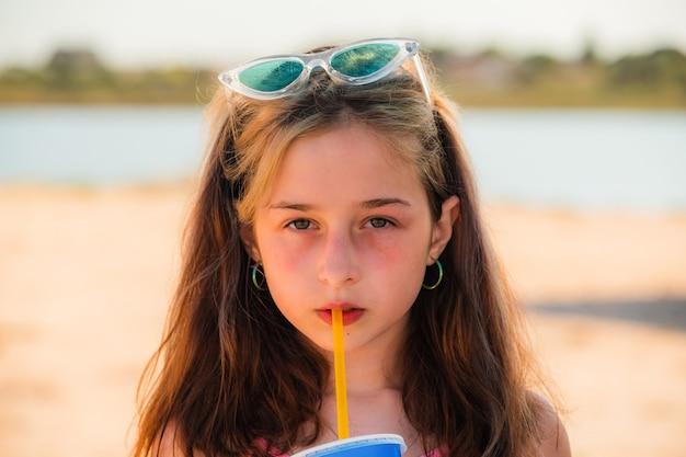 海で10歳の女の子。 10代の若者の肖像画。サングラスをかけた女の子がストローからビーチの海で飲み物を飲みます。