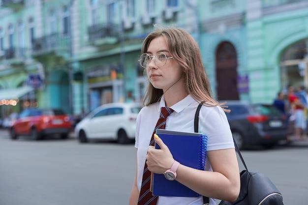 横を向いている街の18歳の女子高生、コピースペース。ネクタイ、メガネ、白いtシャツ、バックパック、ノートブックの女性