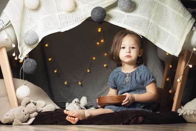 Девушка 2-4 сидит в хижине из стульев и одеял. ребенок играет с игрушками дома
