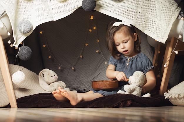 Девушка 2-4 сидит в хижине из стульев и одеял
