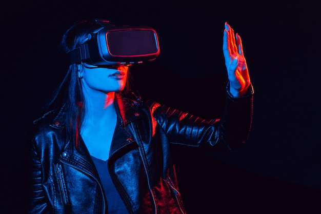 Girl in 3d virtual reality glasses touches the projection screen with her hand