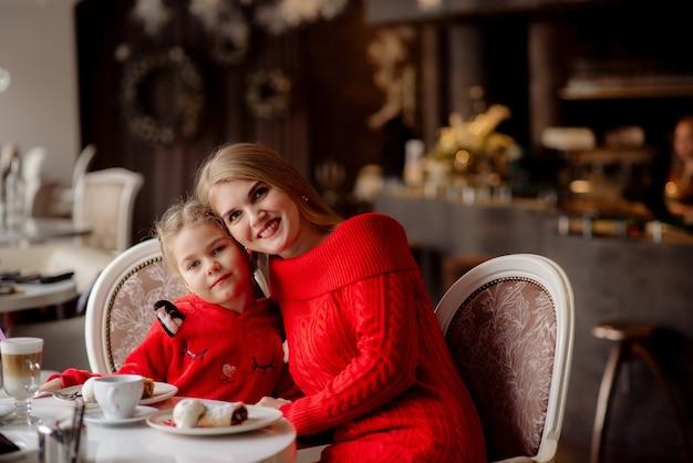 5歳の女の子とお母さんがココアを飲み、カフェでおしゃべり