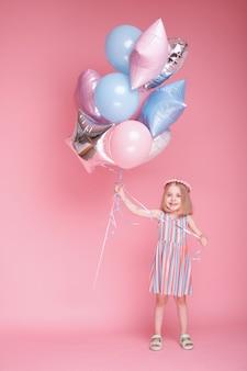 5 세 소녀 놀이와 분홍색 표면에 풍선과 함께 재미를