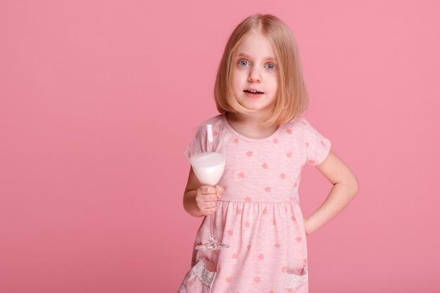 분홍색 표면에 우유와 함께 5 세 소녀