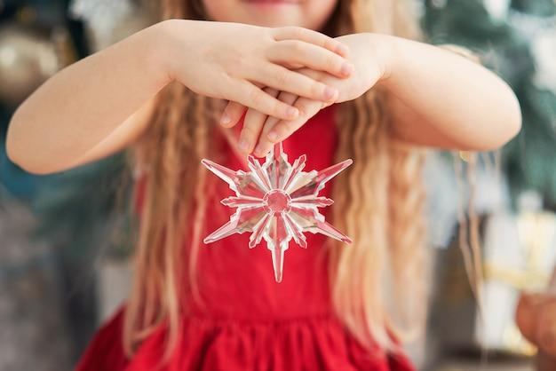 クリスマスツリーの近くの甘いロリポップキャンデー杖を持つ5歳の女の子。