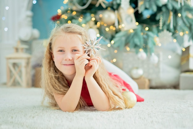 Girl 5 years old with sweet lollipop candy cane near christmas tree.