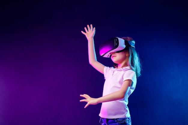 Girl 7 y.o. experiencing vr headset game on colorful . child using a gaming gadget for virtual reality.