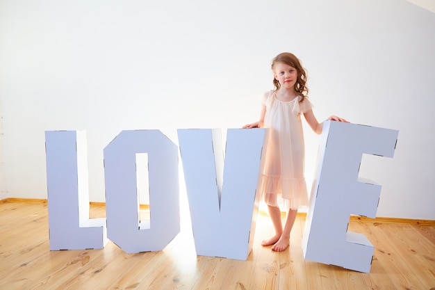 Girl 7 years old playing with big cardboard 3d standing letters forming word love