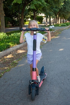 A girl of 8 years old rides an rented electric scooter in the park. kick scooter sharing