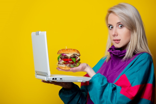Girl in 80s clothes style with burger and notebook making an order