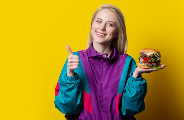 Girl in 80s clothes style with burger