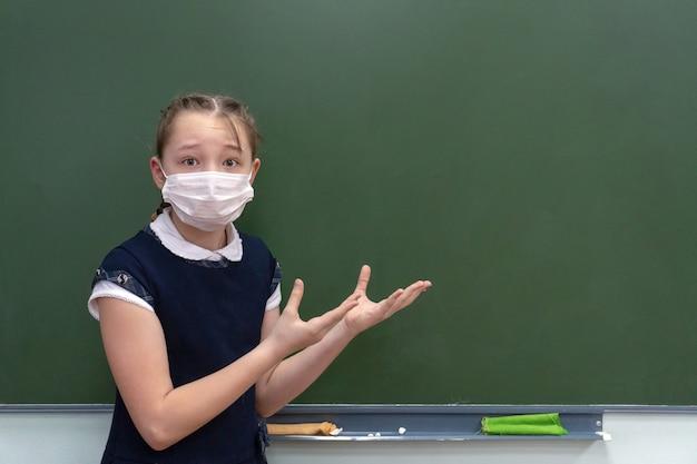 Девочка школьница в медицинской маске стоит у доски и показывает руки на свободное место.