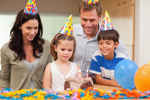 彼女の誕生日のケーキにキャンドルを吹き飛ばす女の子