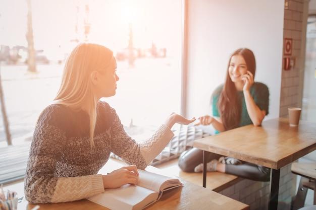 Девушка поглощена чтением книги во время перерыва в кафе