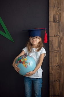 Girl in academic hat and rounded glasses stands at the black wall holding globe behind a ruler, back to school, preschool concept, child is preparing for school