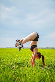 Девушка-акробат выполняет стойку на руках. модель стоит на руках, делает гимнастические шпагаты на фоне зеленой ловушки и голубого неба, занимается спортом на природе.
