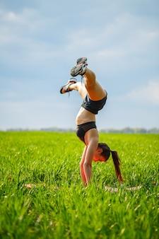 소녀 곡예사는 물구나무서기를 수행합니다. 모델은 손에 서서 녹색 덫과 푸른 하늘을 배경으로 체조를 하고 자연에서 스포츠를 하고 있다