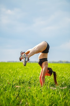 Girl acrobat performs a handstand. the model stands on her hands, doing gymnastic splits against the background of green trap and blue sky, playing sports in nature