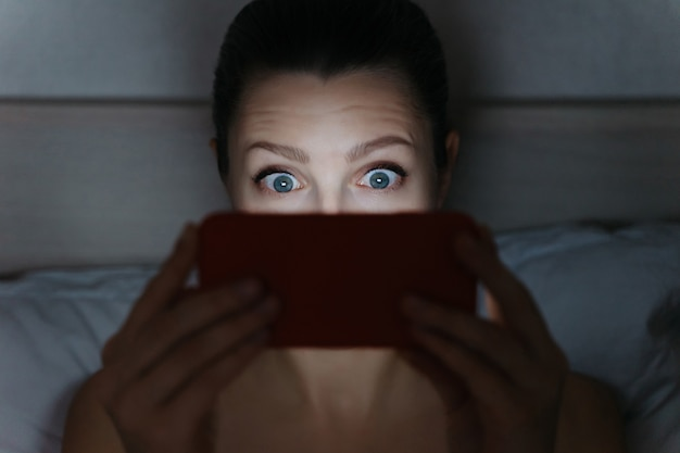 Girl addictively staring at her smartphone late at night in bed.