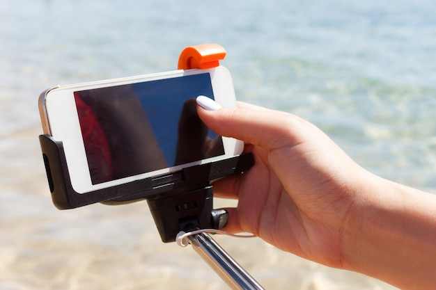 Girl adjusts camera on selfie stick in the sea