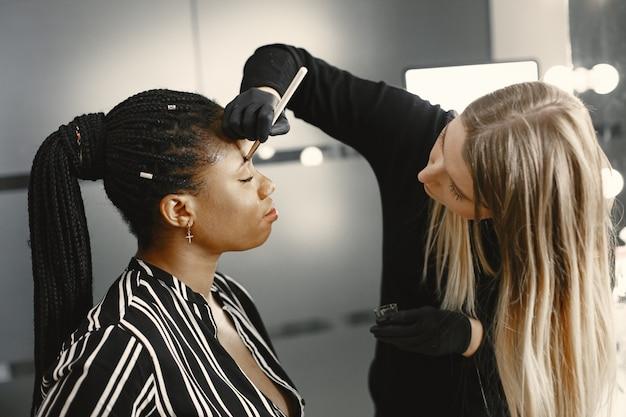 Девушка африка. женщина делает брови. девушки в салоне красоты.