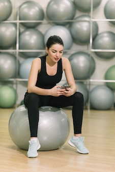 Girl after exercise ball looking at phone