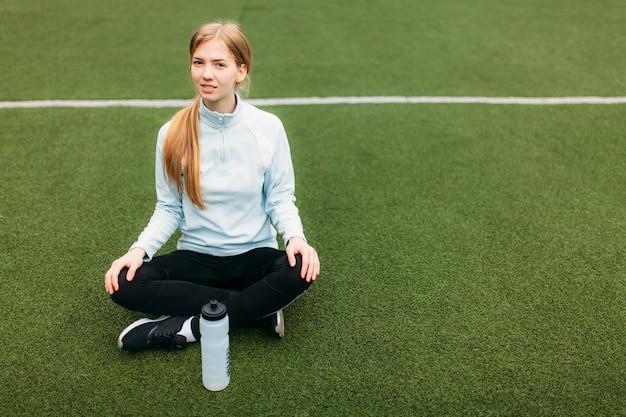 運動後、サッカー場で水を飲む女の子。スポーツウェアの美しい少女の肖像画。