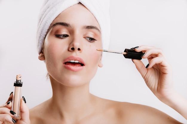 샤워 후 소녀는 컨실러를 눈 아래에 두었습니다. 흰 벽에 아름 다운 여자의 초상화입니다.