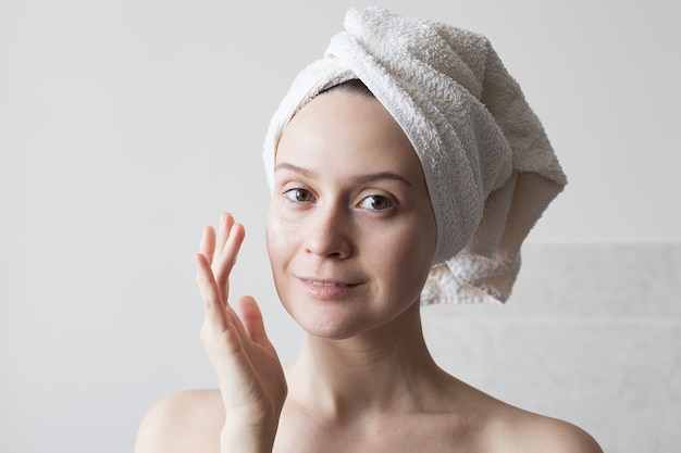 A girl after a shower with a towel on her head applies a moisturizer to her face, daily morning procedures skin care. high quality photo