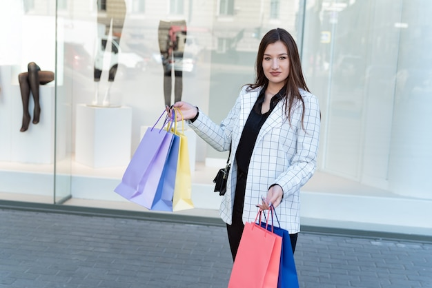 Girl after successful shopping walks past shop windows with multicolored shopping bags