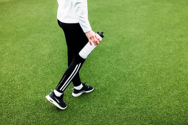 トレーニング、ランニング、スポーツの後の女の子。手前に、水のボトル。少女は、開放的で新鮮な空気の中で働いています。
